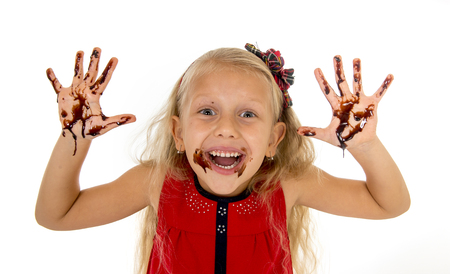 smudgy: pretty little female child with long blond hair and blue eyes wearing red dress showing mouth and dirty hands with stains of chocolate syrup after eating cake smiling happy isolated on white background