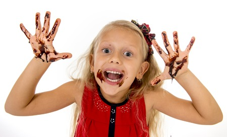 dirty blond: pretty little female child with long blond hair and blue eyes wearing red dress showing mouth and dirty hands with stains of chocolate syrup after eating cake smiling happy isolated on white background