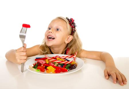 azucar: bastante feliz niña caucásica comer plato lleno de caramelos celebración tenedor en el abuso de azúcar dulce dieta peligrosa y poco saludable nutrición concepto aislado en el fondo blanco Foto de archivo