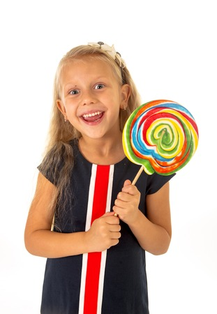 licking in isolated: beautiful female child with long blond hair and blue eyes holding huge spiral lollipop candy smiling happy and excited eating and licking isolated on white background in sugar and sweet concept Stock Photo
