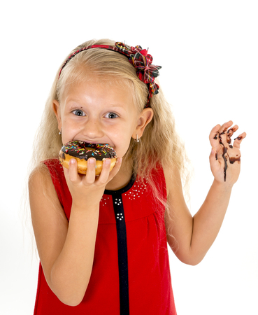 smudgy: beautiful female child with blue eyes and long blond hair in cute red dress eating chocolate donut with syrup stains in mouth and dirty hand smiling happy isolated on white background
