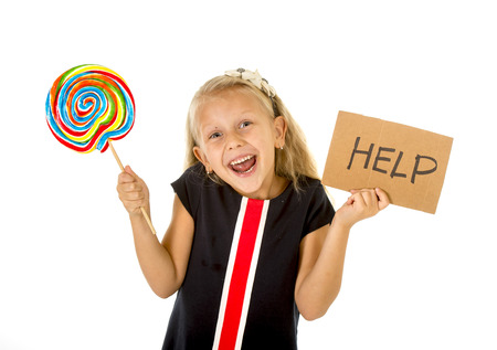 excess: pretty little female child eating big lollipop and holding cardboard help sign in children sugar excess and sweet diet abuse in unhealthy nutrition concept isolated on white background Stock Photo
