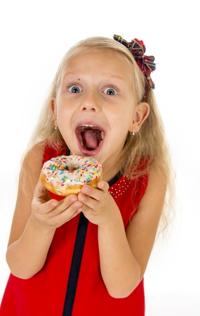 female child: little beautiful female child with long blonde hair and red dress eating sugar donut with toppings delighted and happy isolated on white background in children sweet and sugary nutrition Stock Photo