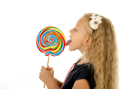 beautiful female child with long blond hair and blue eyes holding huge spiral lollipop candy smiling happy and excited eating and licking isolated on white background in sugar and sweet concept Stock Photo