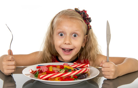 bad habit: pretty little female child with fork and knife eating dish full of candy caramel and sweet food in sugar abuse and unhealthy diet, bad habit nutrition concept isolated on white background Stock Photo