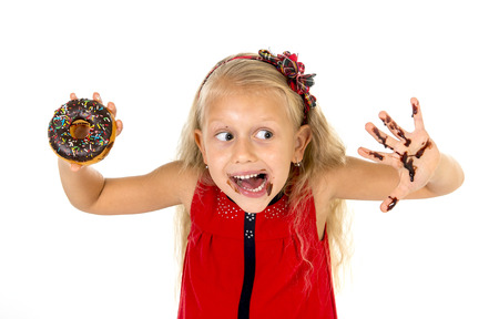 dirty blond: beautiful female child with blue eyes and long blond hair in cute red dress eating chocolate donut with syrup stains in mouth and dirty hand smiling happy isolated on white background
