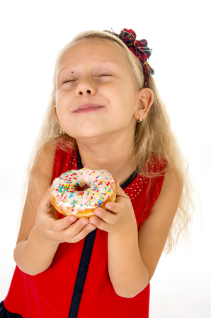 delighted: little beautiful female child with long blonde hair and red dress eating sugar donut with toppings delighted and happy isolated on white background in children sweet and sugary nutrition Stock Photo
