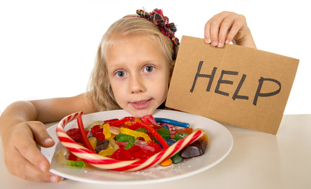 vulnerable: sad and vulnerable Caucasian female child asking for help  eating dish full of candy and gummies holding sugar spoon in sweet abuse dangerous diet and unhealthy nutrition concept isolated on white