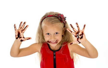 smudgy: pretty little female child with long blond hair wearing red dress showing mouth and dirty hands with stains of chocolate syrup after eating cake smiling happy isolated on white background