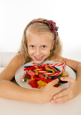 bad diet: pretty little female child eating dish full of candy caramel and sweet food in sugar abuse and unhealthy diet, bad habit nutrition concept isolated on white background