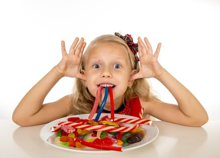 bad habit: pretty little female child eating dish full of candy caramel and sweet food in sugar abuse and unhealthy diet, bad habit nutrition concept isolated on white background