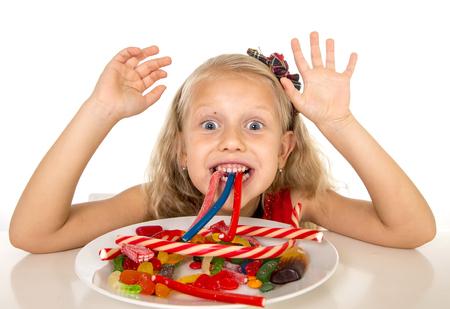 niños rubios: bastante feliz niña caucásica comer plato lleno de dulces en el abuso de azúcar dulce dieta peligrosa y poco saludable nutrición concepto aislado en el fondo blanco