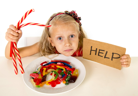 sugar spoon: sad and vulnerable Caucasian female child asking for help  eating dish full of candy and gummies holding sugar spoon in sweet abuse dangerous diet and unhealthy nutrition concept isolated on white