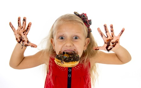 dirty blond: pretty little female child with long blond hair wearing red dress biting donut mouth showing dirty hands with stains of chocolate syrup after eating cake smiling happy isolated on white background