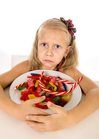 vulnerable: pretty vulnerable Caucasian female child eating dish full of candy holding the dish in sweet sugar abuse dangerous diet and unhealthy nutrition concept isolated on white background