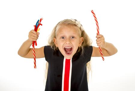 poco: pequeña y hermosa niña con ojos azules, dulces y pelo largo y rubio que come el caramelo de regaliz de fresa y la celebración de un montón de gomitas sonriente feliz aisladas sobre fondo blanco