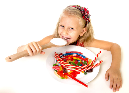 sugar spoon: pretty happy Caucasian female child eating dish full of candy holding sugar spoon in sweet caramel abuse dangerous diet and unhealthy nutrition concept isolated on white background