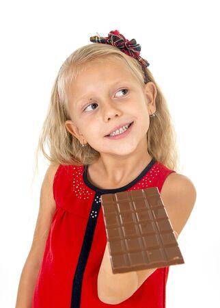 cabello rubio: peque�a ni�a hermosa en vestido rojo que sostiene feliz barra de delicioso chocolate en sus manos comer encantados en los ni�os el az�car y la adicci�n dulce aislado en el fondo blanco
