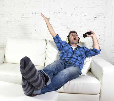 alone: young attractive 20s or 30s man having fun alone lying on home couch listening to music holding mobile phone as microphone using headphones singing passionate happy and crazy