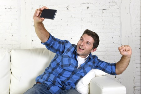 taking video: young attractive 30s man taking selfie photo or self video with mobile phone at home sitting on couch smiling happy in use of technology and image concept Stock Photo