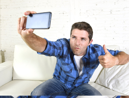 self image: young attractive 30s man taking selfie picture or self video with mobile phone at home sitting on couch smiling happy giving thumbs up in use of technology and image concept