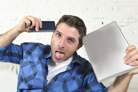 work addicted: young internet and technology addict man at home couch networking with mobile phone and digital tablet device looking crazy and in stress in social network addiction Stock Photo