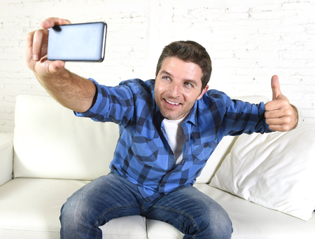 taking video: young attractive 30s man taking selfie photo or self video with mobile phone at home sitting on couch smiling happy giving thumbs up in use of technology and image concept