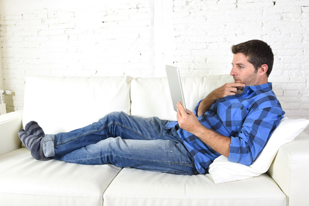 living room: young attractive 30s man using digital tablet pad lying on couch at home living room networking looking relaxed and happy in portable technology and internet concept Stock Photo