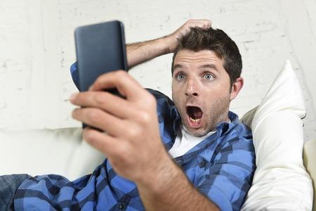 sorprendido: joven atractiva, acostado en el sofá en casa utilizando internet en su teléfono móvil que mira sorprendido y conmocionado tirar del pelo en la tecnología concepto de estrés