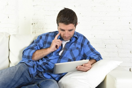 eye pad: young attractive 30s man using digital tablet pad lying on couch at home living room networking looking relaxed and happy in portable technology and internet concept Stock Photo