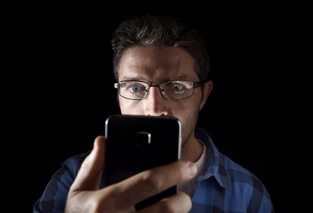 head light: close up portrait of young man looking intensively to mobile phone screen with blue eyes wide open isolated on black background on dark edgy lighting scheme in addiction to internet technology