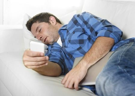 sleeping pad: young attractive man in shirt and jeans sleeping at home couch with mobile phone and digital tablet pad in his hands  in internet technology addiction and lifestyle concept