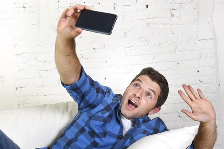 taking video: young attractive 30s man taking selfie picture or self video with mobile phone at home sitting on couch smiling happy in use of technology and image concept