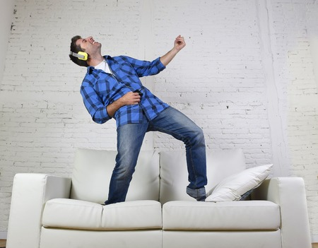 young attractive 20s or 30s man having fun jumped on home couch listening to music on mobile phone with headphones dancing , singing and playing air guitar happy and crazy
