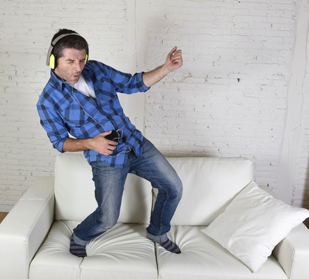 room air: young attractive 20s or 30s man having fun jumped on home couch listening to music on mobile phone with headphones dancing , singing and playing air guitar happy and crazy