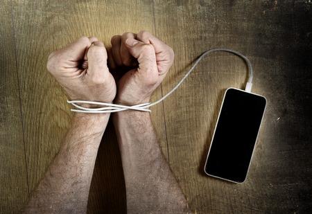 celulas humanas: las manos del hombre atrapados y envueltos en las muñecas con cable de teléfono móvil como esposas en las redes de teléfonos inteligentes y tecnología de la comunicación concepto de adicción Foto de archivo