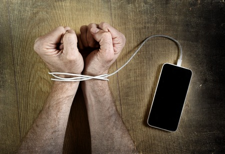 junkie: man hands trapped and wrapped on wrists with mobile phone cable as handcuffs in smart phone networking and communication technology addiction concept Stock Photo