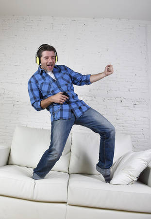 air guitar: young attractive 20s or 30s man having fun jumped on home couch listening to music on mobile phone with headphones dancing , singing and playing air guitar happy and crazy