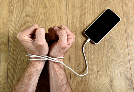 handcuffs: man hands trapped and wrapped on wrists with mobile phone cable as handcuffs in smart phone networking and communication technology addiction concept Stock Photo