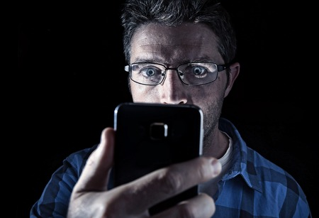 eyes wide: close up portrait of young man looking intensively to mobile phone screen with blue eyes wide open isolated on black background on dark edgy lighting scheme in addiction to internet technology
