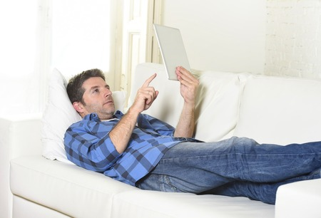 30s: young attractive 30s man using digital tablet pad lying on couch at home living room networking looking relaxed and happy in portable technology and internet concept Stock Photo