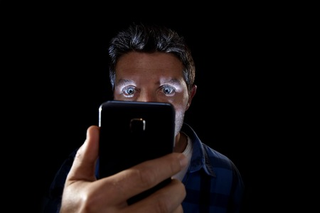 eyes wide open: close up portrait of young man looking intensively to mobile phone screen with blue eyes wide open isolated on black background on dark edgy lighting scheme in addiction to internet technology