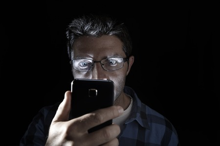 dark backgrounds: close up portrait of young man looking intensively to mobile phone screen with blue eyes wide open isolated on black background on dark edgy lighting scheme in addiction to internet technology