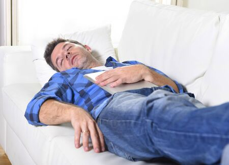 sleeping pad: young attractive man in shirt and jeans sleeping at home white couch in living room having a rest after working with digital tablet pad in internet technology addiction and lifestyle concept