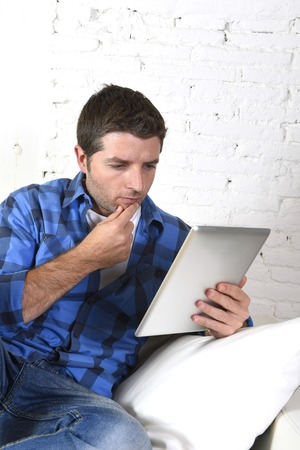 thoughful: young attractive 30s man using digital tablet pad lying on couch at home living room networking looking relaxed and thoughful in portable technology and internet concept Stock Photo