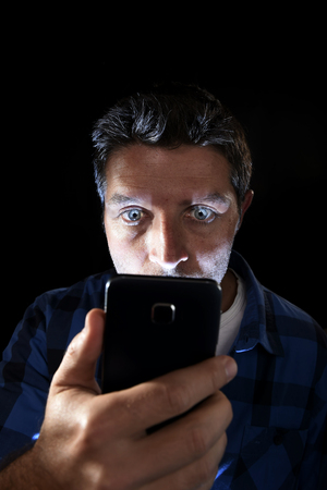 cell phone addiction: close up portrait of young man looking intensively to mobile phone screen with blue eyes wide open isolated on black background on dark edgy lighting scheme in addiction to internet technology