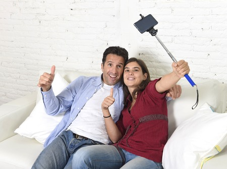 taking video: attractive couple taking selfie photo or shooting self video with mobile phone and stick sitting at home couch smiling happy together celebrating their love in technology image concept Stock Photo