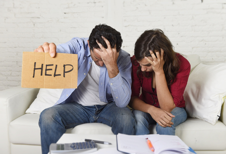 home expenses: young couple worried need help in stress at home couch accounting debt bills bank papers expenses and payments feeling desperate in bad financial situation