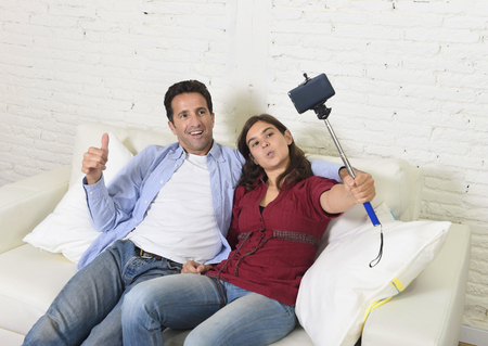 taking video: young attractive couple taking selfie photo or shooting self video with mobile phone and stick sitting at home couch smiling happy together celebrating their love in technology image concept Stock Photo