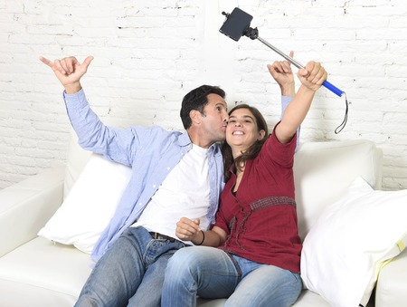 taking video: young attractive couple taking selfie photo or shooting self video with mobile phone and stick sitting at home couch smiling happy together man kissing woman celebrating their love Stock Photo